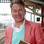 Michael Portillo standing on a train platform with tracks in the background, wearing a blue top and pink blazer. He's smiling at the camera holding a book.
