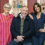 Keith Brymer Jones sits on a stool with Sue Pryke and Melanie Sykes stood besides him smiling at the camera. Wooden wall with varied containers is in the background.