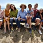 The main cast is sitting on a beach posing for the camera