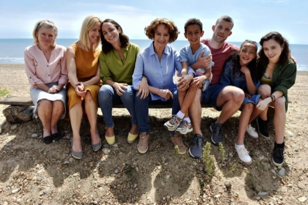 The main 8 cast members sitting on a bench on the beach posing for the camera with the sea behind.