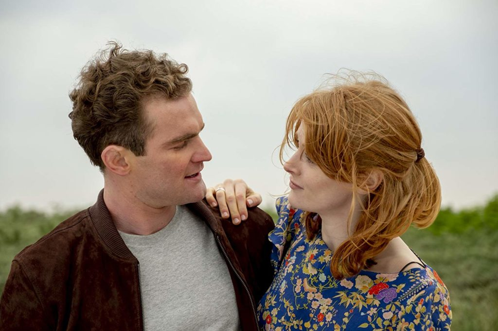 Mark Stanley (David Tait) wearing a brown jacket and Emily Beecham (Vanessa Tait) wearing a blue floral dress, looking at each other with greenery and sky behind them.