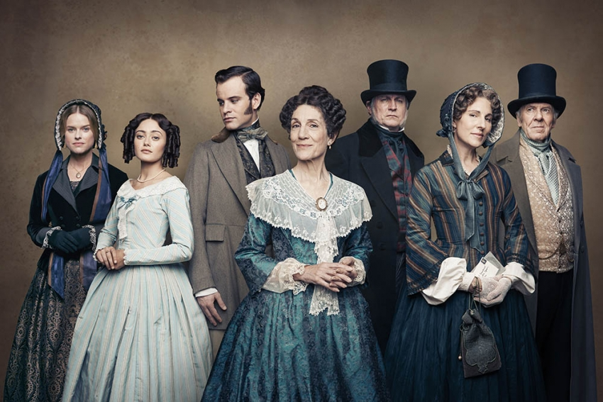 The cast of Belgravia standing in a row wearing period costumes in front of a brown backdrop.
