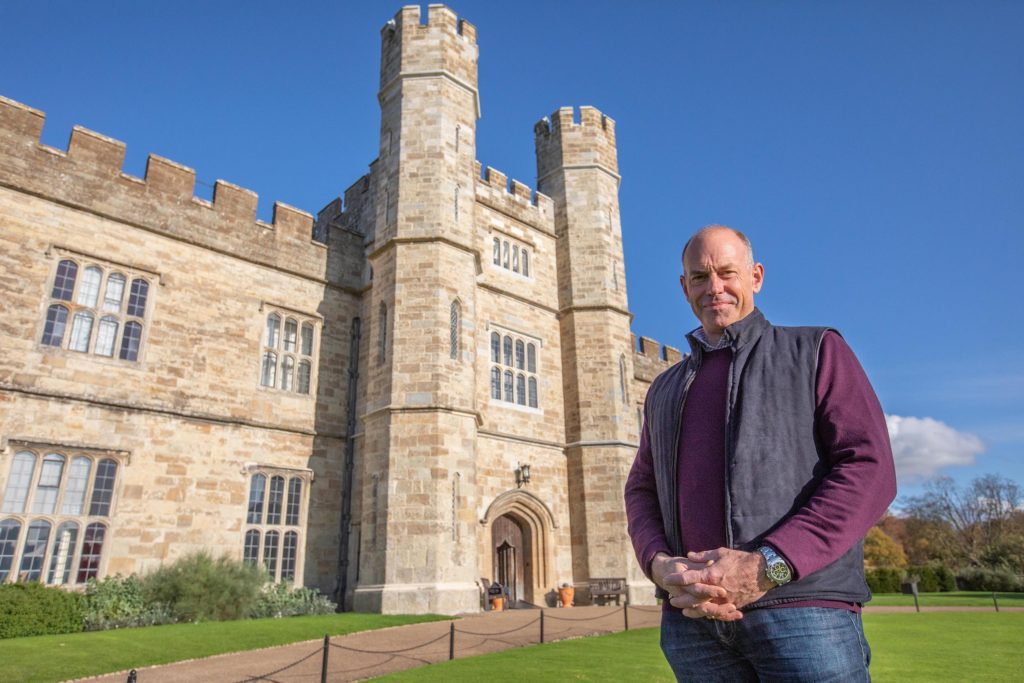 Phil Spencer wearing a purple jumper standing on the grass in front of the entrance to Leeds Castle.