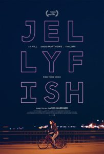 Jellyfish Poster- A woman riding a bike in a coat along the seafront at night is at the bottom of the poster with the jellyfish text at the top.