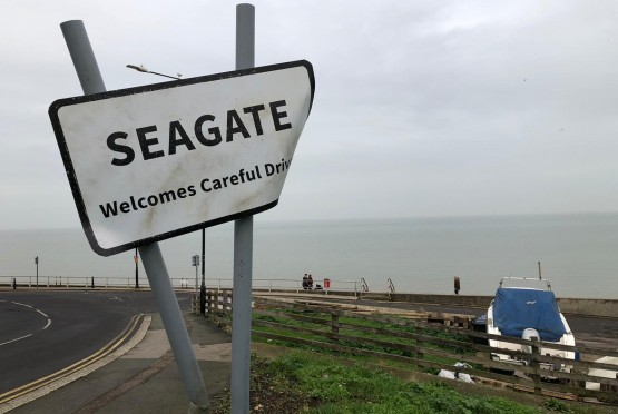 A damaged road sign saying 'Seagate' on the side of a coastal road with the sea in background.