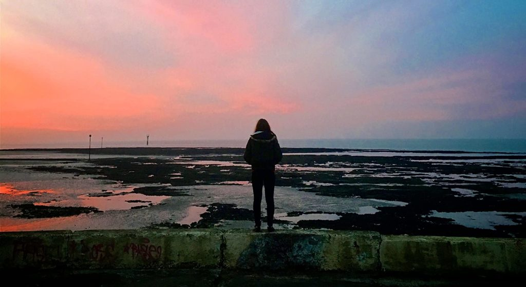 Liv Hill stands on a deserted beach wearing a coat looking out at the pink sunset over the low tide.