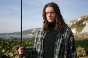 A production still showing Gabrielle Sheppard dressed in a black checkered shirt stood against a beach cliffs background holding a metal rod.