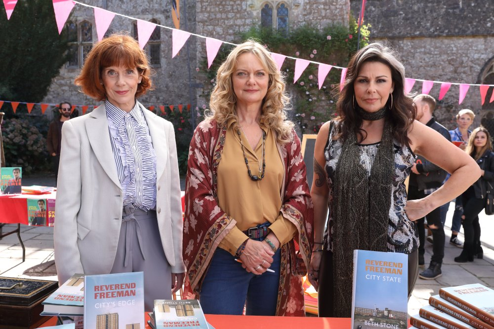 Cast Julie Graham, Siobhan Redmond, and Sarah Woodward standing by a table full of books outside a church with bunting in the background.