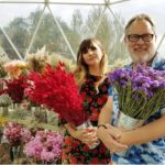 Presenters Natasia Demetriou and Vic Reeves standing in display pavilion holding flowers