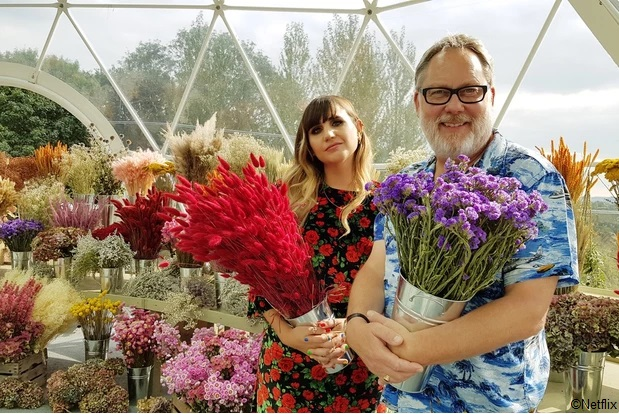 Presenters Natasia Demetriou and Vic Reeves standing in display pavilion holding flowers with flowers behind them.