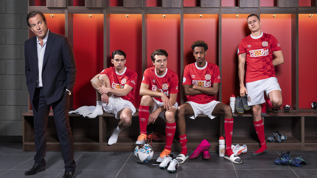 Actors Theo Barklem-Biggs, Shaquille Ali-Yebuah, Jake Short, Jack McMullen, Will Arnett sitting on a bench in front of a set of lockers wearing red football shirts