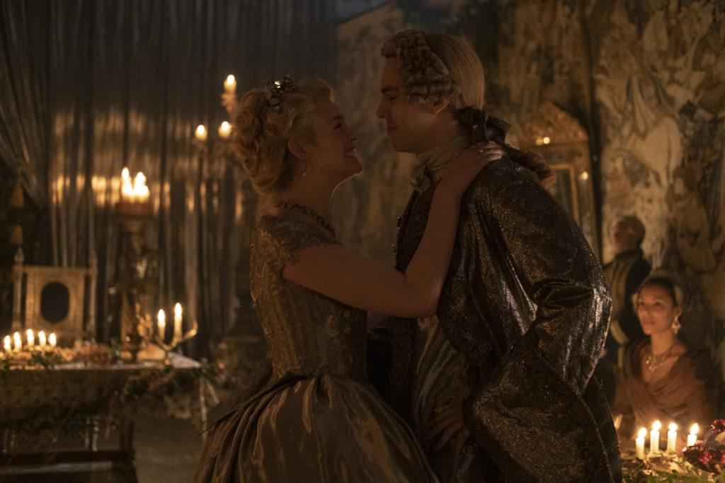 Catherine the Great (Elle Fanning) and Peter III (Nicholas Hoult) dancing in a ballroom in historical costumes, with candlelight in the background.