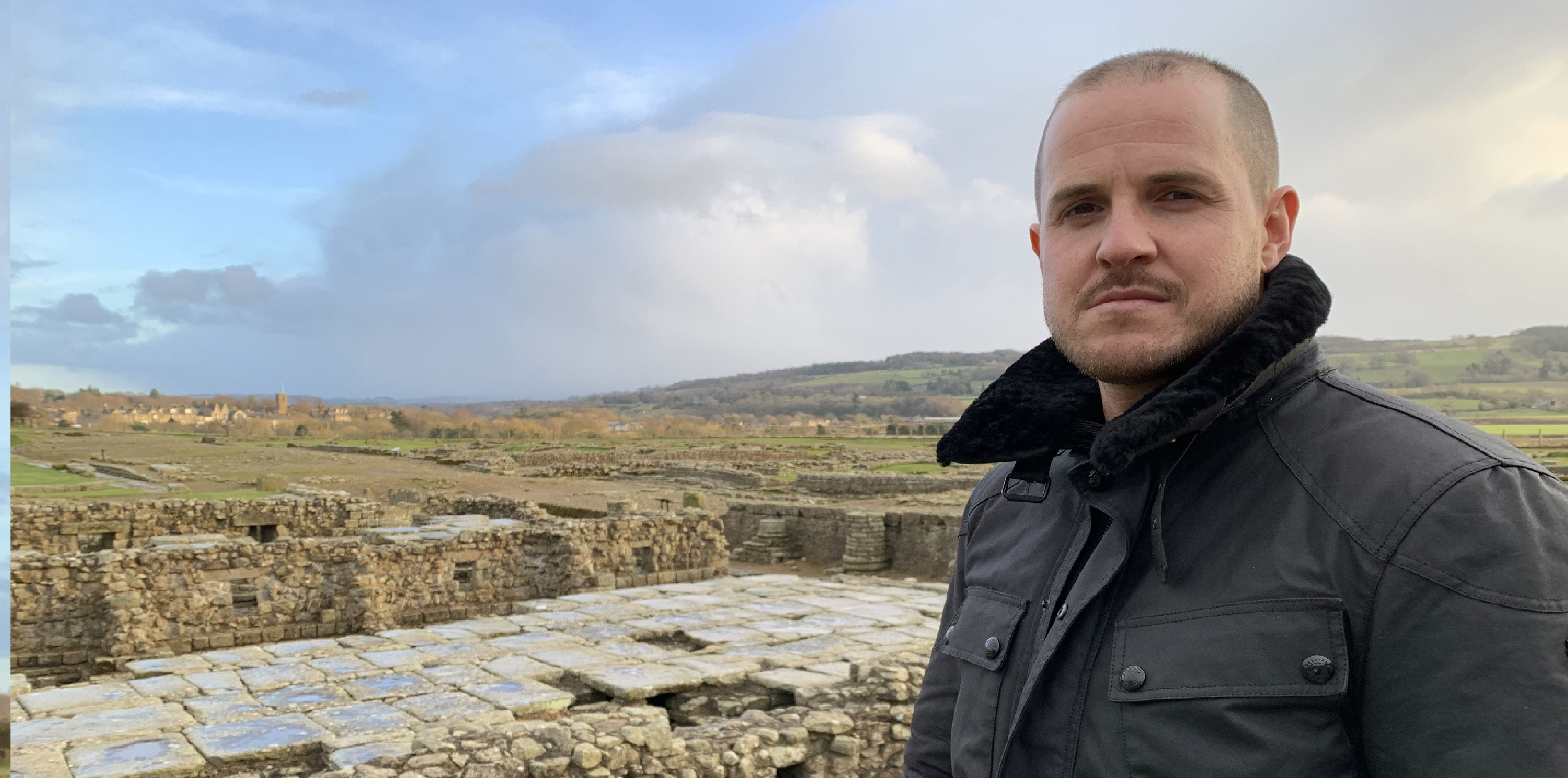 Presenter Dan Jones looking at the camera with a Roman road behind him.