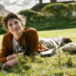 Alice (Gemma Arterton) laying on the grass with a book smiling at the camera with white cliffs as a backdrop.