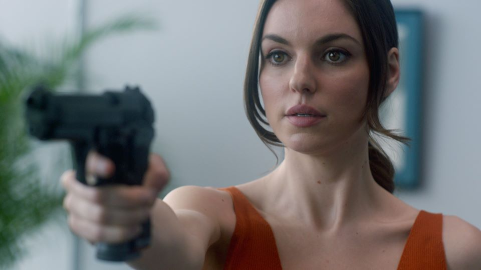 Michelle Mylett wearing an orange top points a hand gun towards the camera. White walls and plants are behind her.