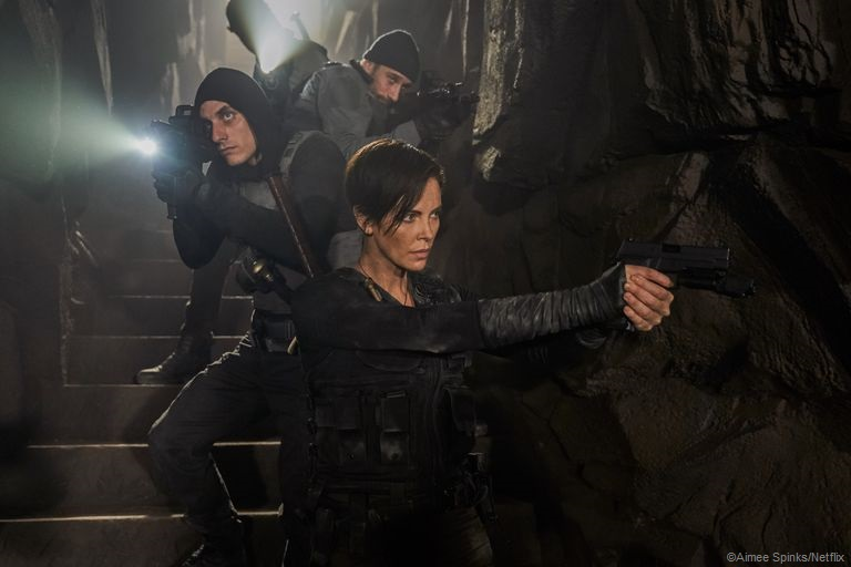 Actor Charlize Theron in the front centre pointing her gun off camera, 3 other male cast members are lined up behind her on the stairs of a cave with their guns pointed