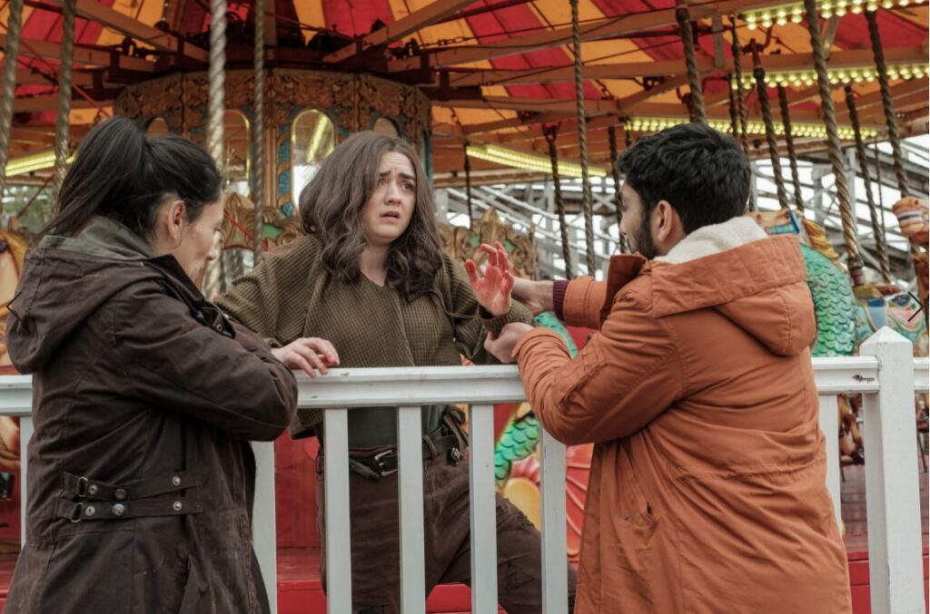 Actors Sian Clifford, Maisie Williams and Mawaan Rizwan stand in front of a merry-go-round.