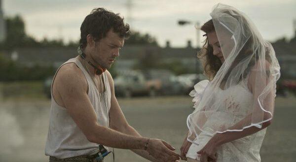 Actor Alden Ehrenreicht touching actress Lara Peake's pregnant stomach. She is dressed in a wedding dress