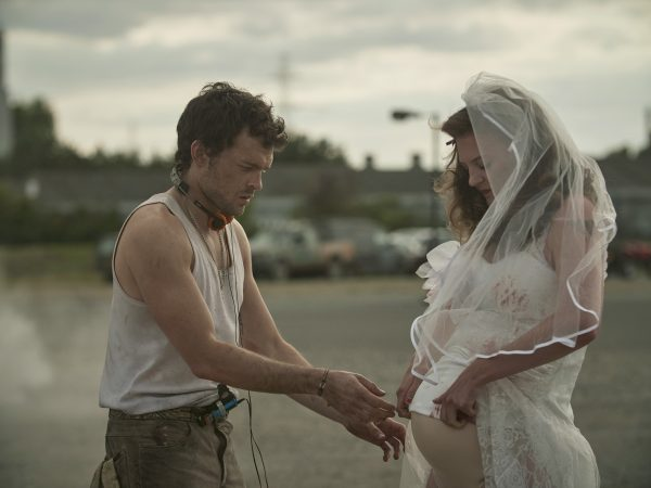 Actor Alden Ehrenreicht touching actress Lara Peake's pregnant stomach. She is dressed in a wedding dress