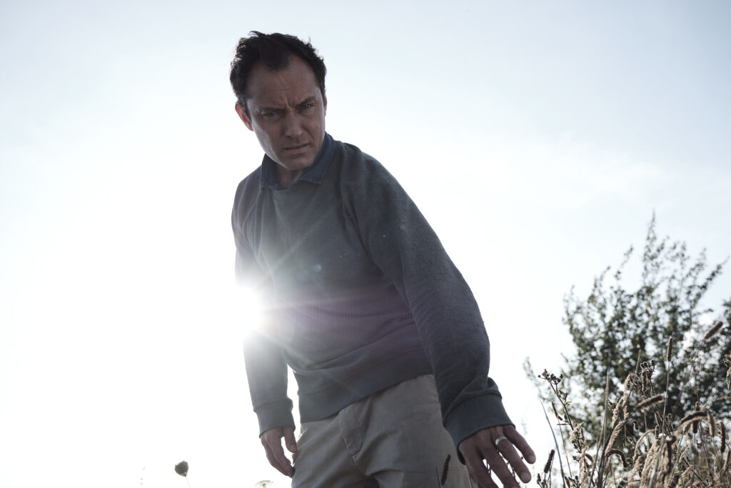 Jude Law as character Sam stands silhouetted by the sun looking towards the ground