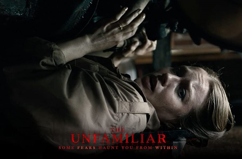 The Unfamiliar Film Poster – Actress Jemima West as Elizabeth (Izzy) Cormack hides under a car looking frightened. She wears brown overalls. The film title at the bottom is in red with the strapline 'some fears haunt you from within'.