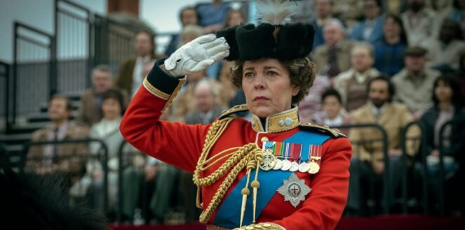 Actress Olivia Coleman as Queen Elizabeth II dressed in regimental uniform sitting on a black horse saluting. In the background is a crowd