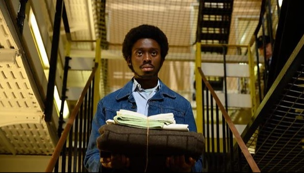 Actor Sheyi Cole as Alex Wheatle in a prison scene wearing blue overalls carrying a pile of clothing. Behind him is the prison metal stair case and walkways.