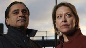 The image shows head shots of actors Sanjeev Bhaskar and Nicola Walker looking into the distance. Sanjeev wears a black coat and Nicola wears a red coat.