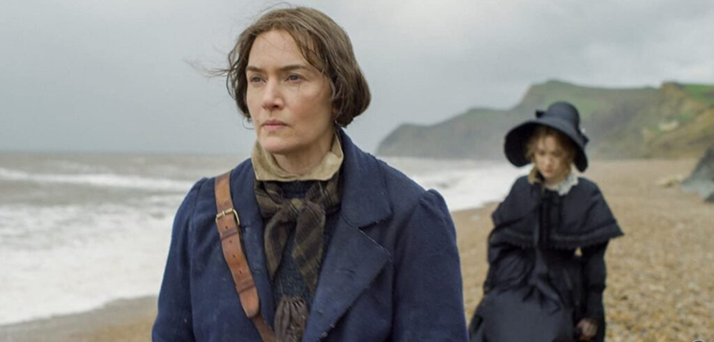 Kate Winslet as Mary AnningandSaoirse Ronanas Charlotte Murchison inAmmonite walking along a beach in Lyme Regis. Kate wears a blue coat and brown frock, her hair is plainly tied back and she carries a leather satchel across her shoulder. Saoirse wears a bonnet and black dress and walks behind. Waves are breaking behind them onto the beach and the cliffs are shrouded in mist..