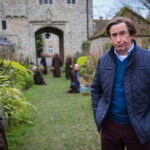 Actor Alan Partridge stands in the foreground on grass wearing a blue jumper and jacket and is pulling a silly expression. Behind him is a stone archway and monks gardening.