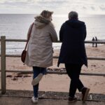 Daisy Haggard as Ally and Martin Freeman as Paul lean against railings overlooking a beach with their backs to the camera. Daisy has blonde hair and wears a cream hooded coat and blue jeans. Martin wears a black coat and dark jeans. In the distance is a couple on the beach by the sea