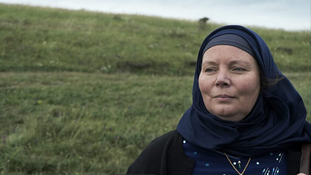 Actress Joanna Scanlan as Mary Hussain in a scene from the film. Joanna wears a patterned top and black headscarf and is looking into the distance. Behind her is grass.