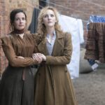 Laura Donnelly and Ann Skelly are standing arm in arm looking into the distance. They are dressed in Victorian clothes in a London street with washing hanging behind them.