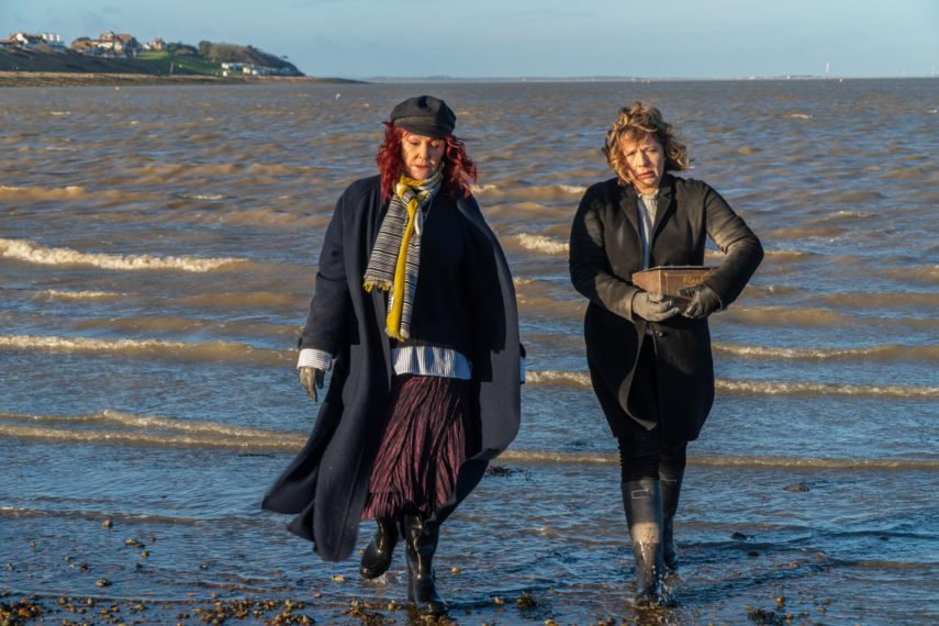 A woman with red hair and a black hat (Frances Barber as Dolly) walks along the sea shore with a woman wearing a black coat carrying a box (Kerry Godliman as Pearl Nolan). In the distance is the shoreline with houses and a beach