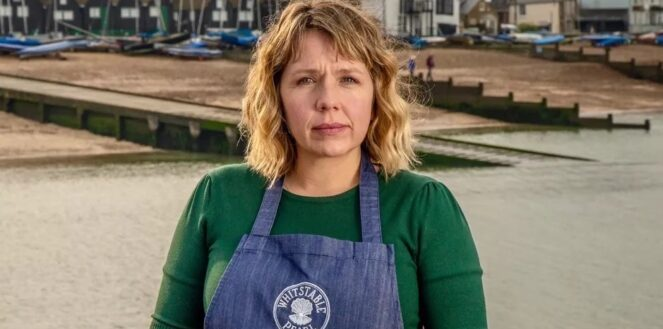 Kerry Godliman as restaurant owner Pearl Nolan is centre of the image wearing a green top and blue apron. She has blonde hair and behind her is a pebble beach with boats and fishing huts