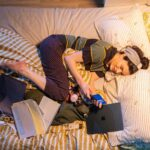 The image is an overhead view of Aisling Bea as Aine lying on an unmade bed. She is wearing a stripey purple, grey and yellow top, grey hairband and red and black pyjama bottoms. She is holding a phone and on the bed is a messy pile of paperwork, a laptop and other small items.