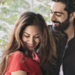 Jhataleka Malhotra as Sia and Anmol Dhillon as Varun are stood together smiling with trees behind them. The man has black hair and a beard and wears a black jacket, and the woman has long brown hair and wears a red top.