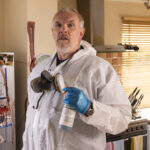 Greg Davies as Paul 'Wicky' Wickstead is stood in a kitchen wearing white overalls and blue gloves and has a face mask around his neck. He has grey hair and a moustache and beard. Behind him is a fridge covered in blood.