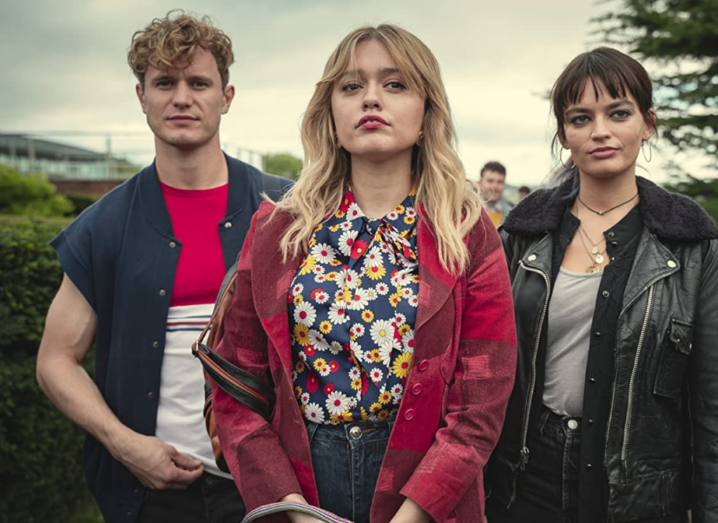 Three actors pose in character outside a school. The background shows a building to the left and some trees. The two actors left and centre are dressed in colourful clothing and the actor on the right wears black and grey.