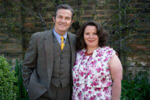 Pa and Ma Larkin posing for a photo in front of a brick wall with a pear tree. Bradley Walsh as Pa Larkin wears a tweed suit, blue shirt and yellow tie. Joanna Scanlan as Ma Larkin wears a pink and white floral dress.