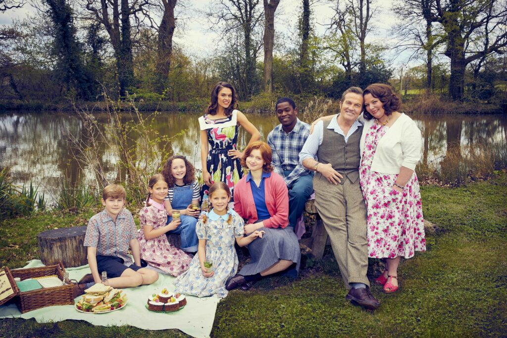 The Larkins family posing for a photo by a lake with trees in the background. The actors are wearing brightly coloured 1950s clothing. To the left children sit on a picnic blanket with a hamper. The adults stand to the right leaning on a wooden bench.